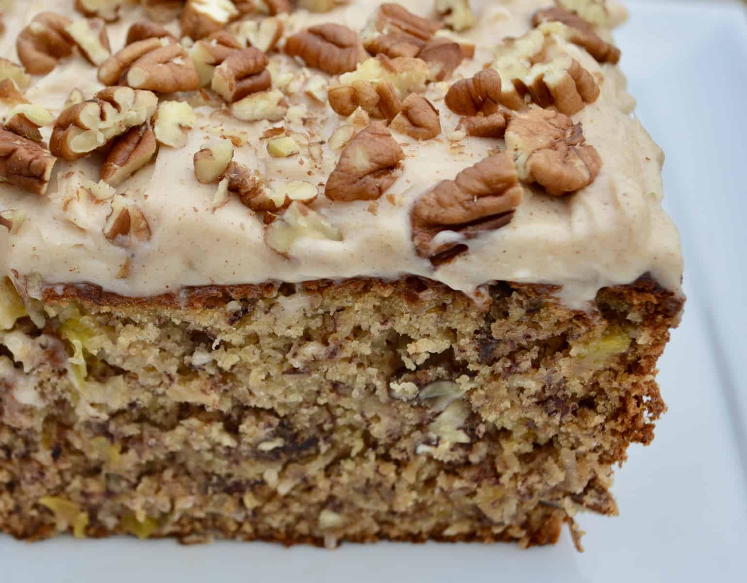 Hummingbird Bread with cinnamon cream cheese frosting topped with chopped pecans