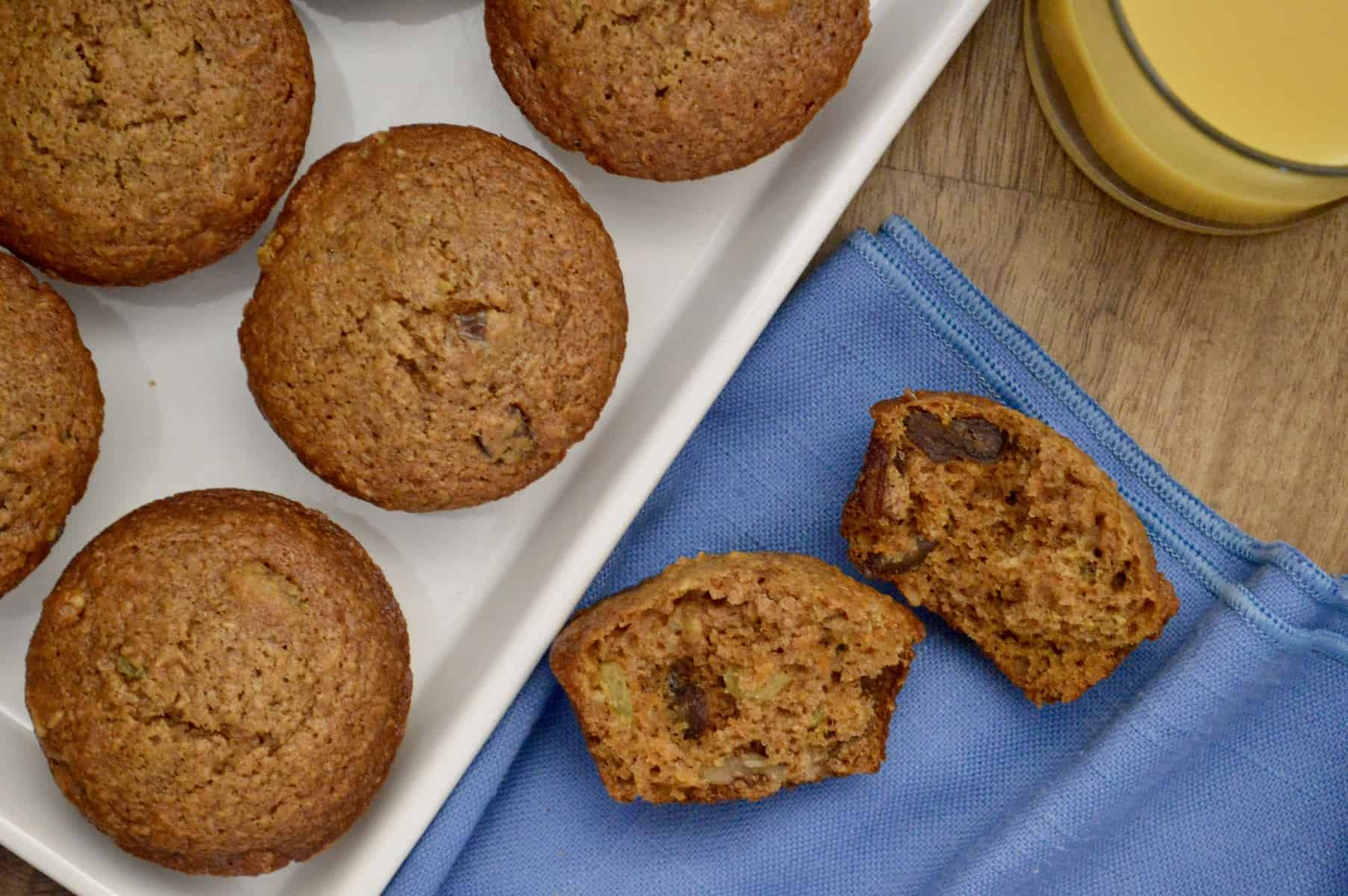 healthy carrot muffins on a white plate with a glass of orange juice on the side