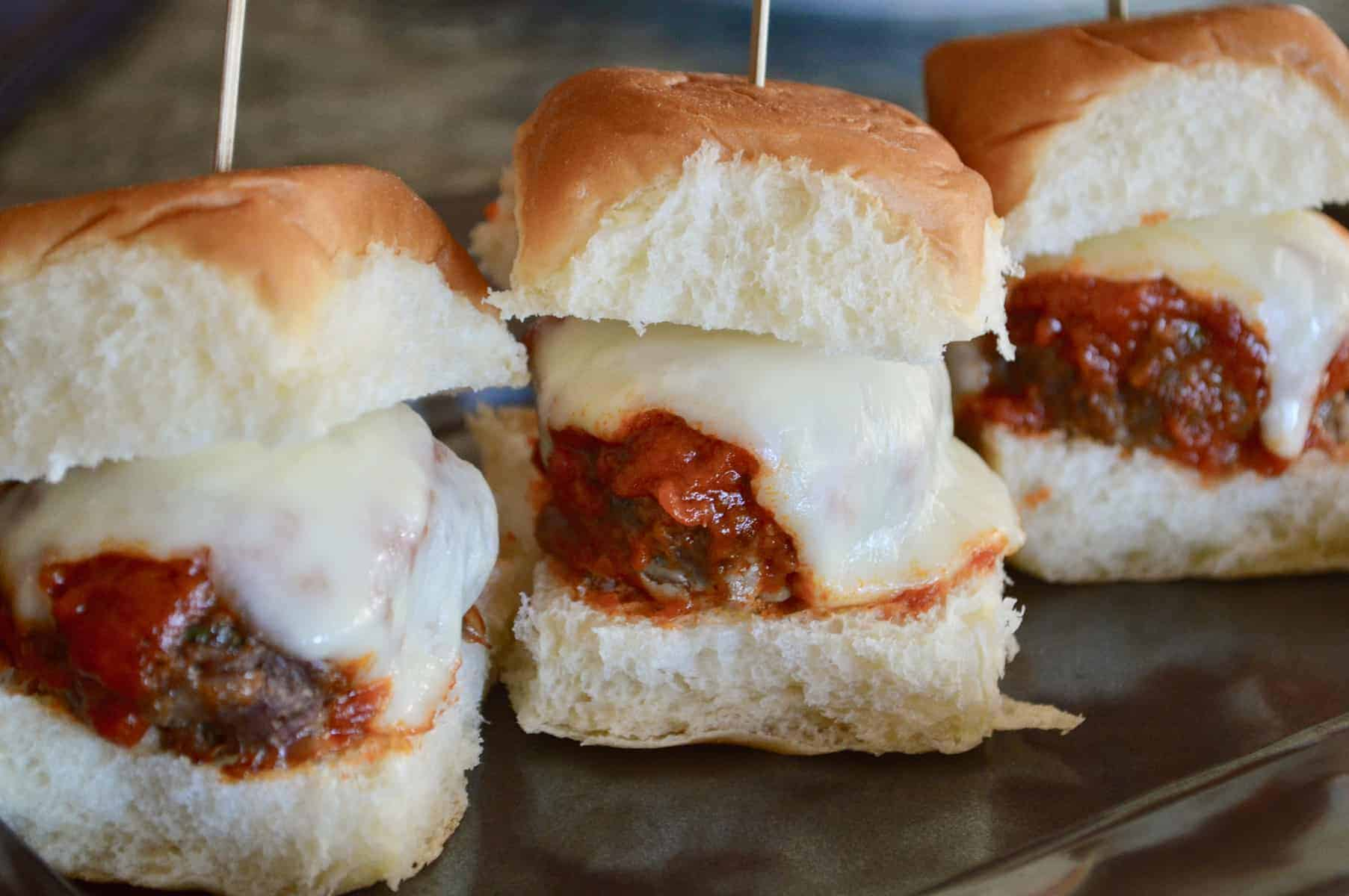 Easy Italian Meatball Sliders on a black plate with skewers in them