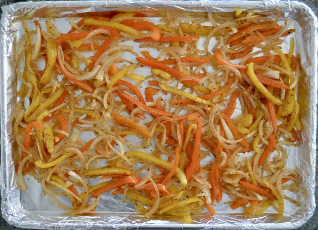 onions and bell peppers on a foil lined baking sheet