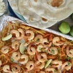 Sheet Pan Shrimp Fajita dinner set up with tortillas and lime