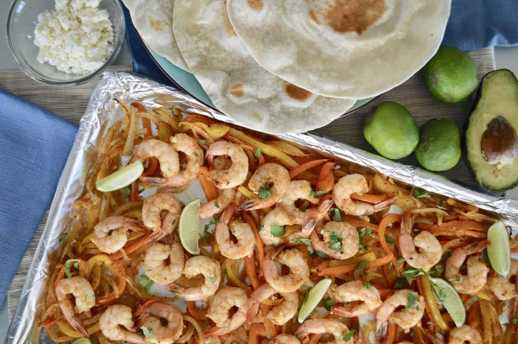 Sheet Pan Shrimp Fajita dinner set up with tortillas and lime