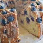 Blueberry Lemon Bundt Cake baked in a Jubilee Pan and garnished with blueberries and honey lemon drizzle