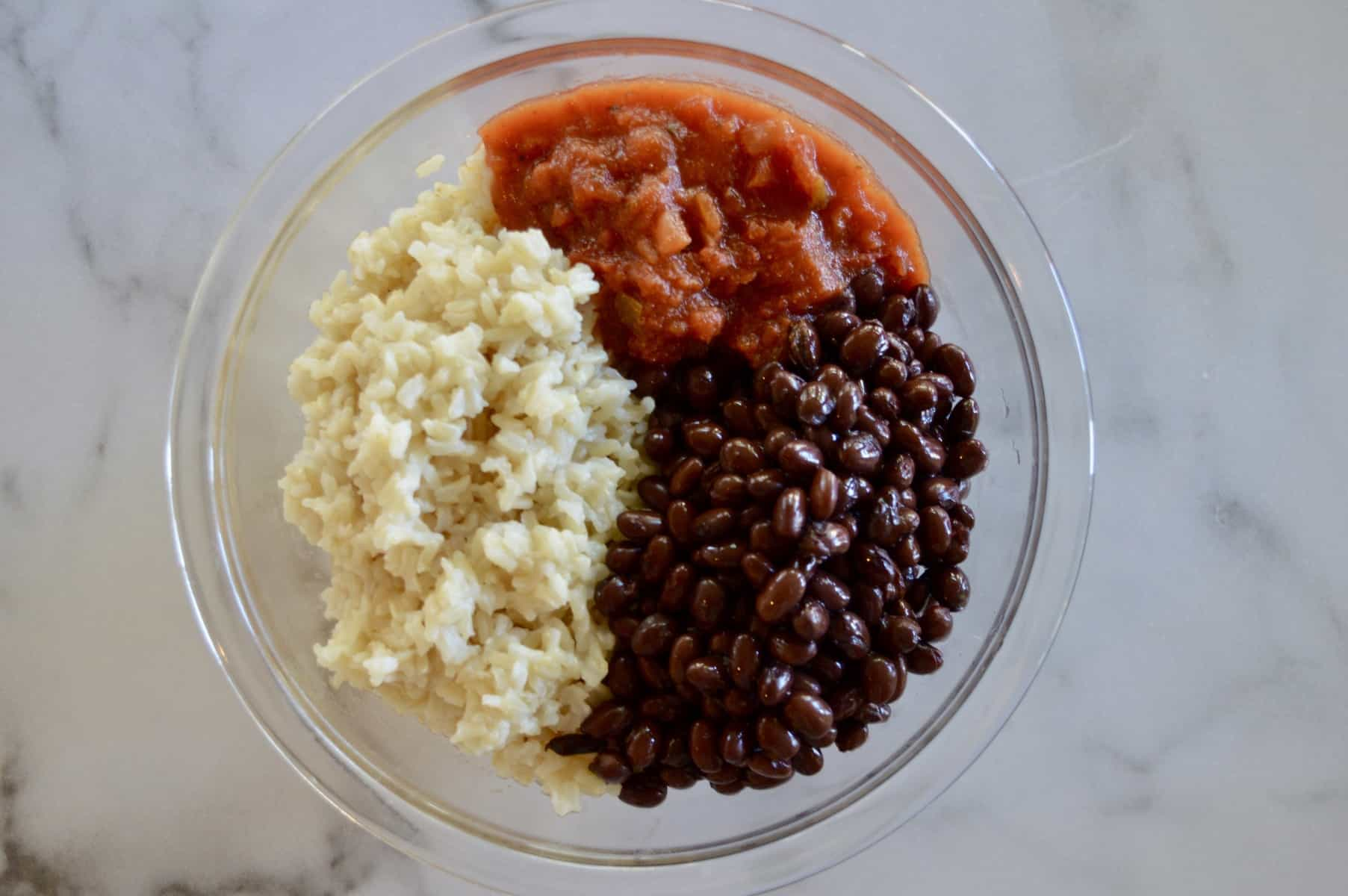 brown rice, black beans, and salsa in a glass bowl