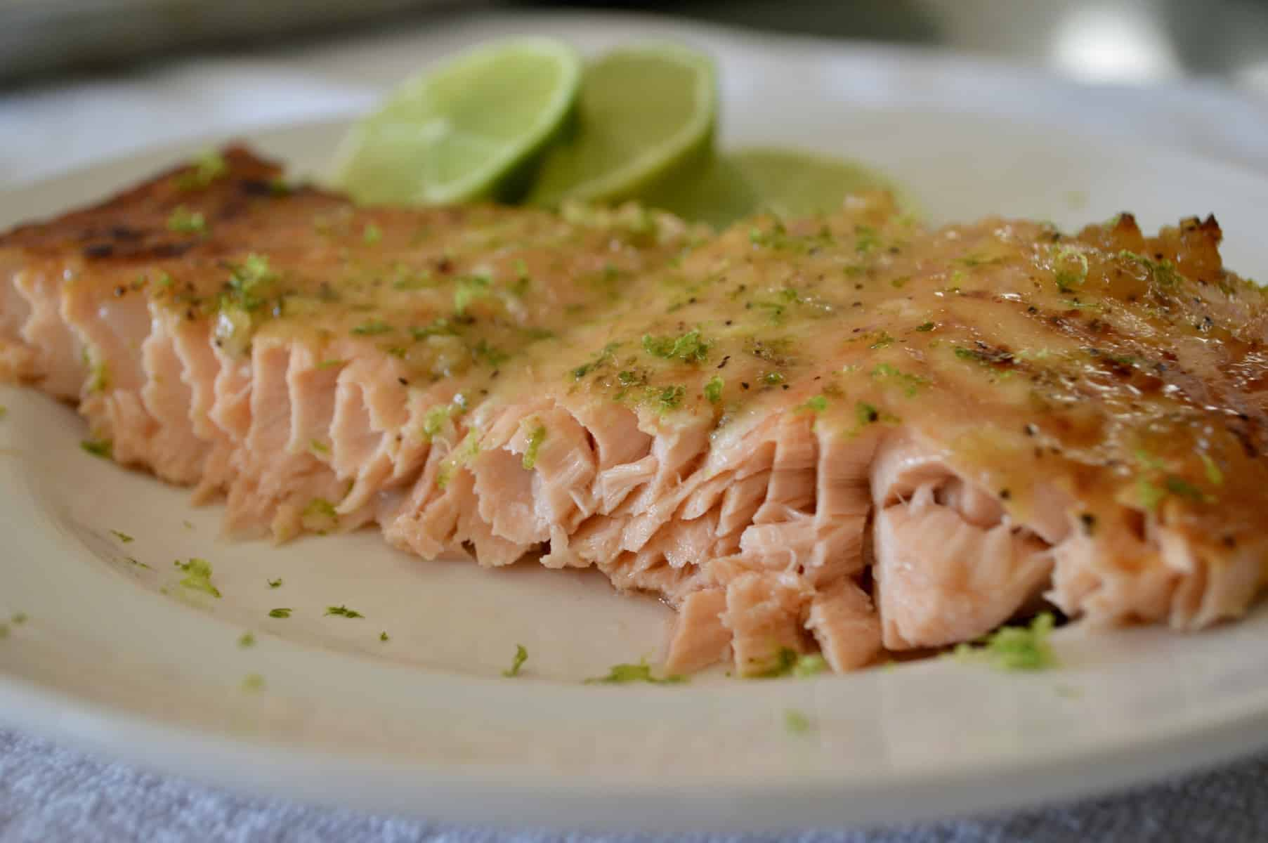 Honey lime Salmon on a white plate with lime slices