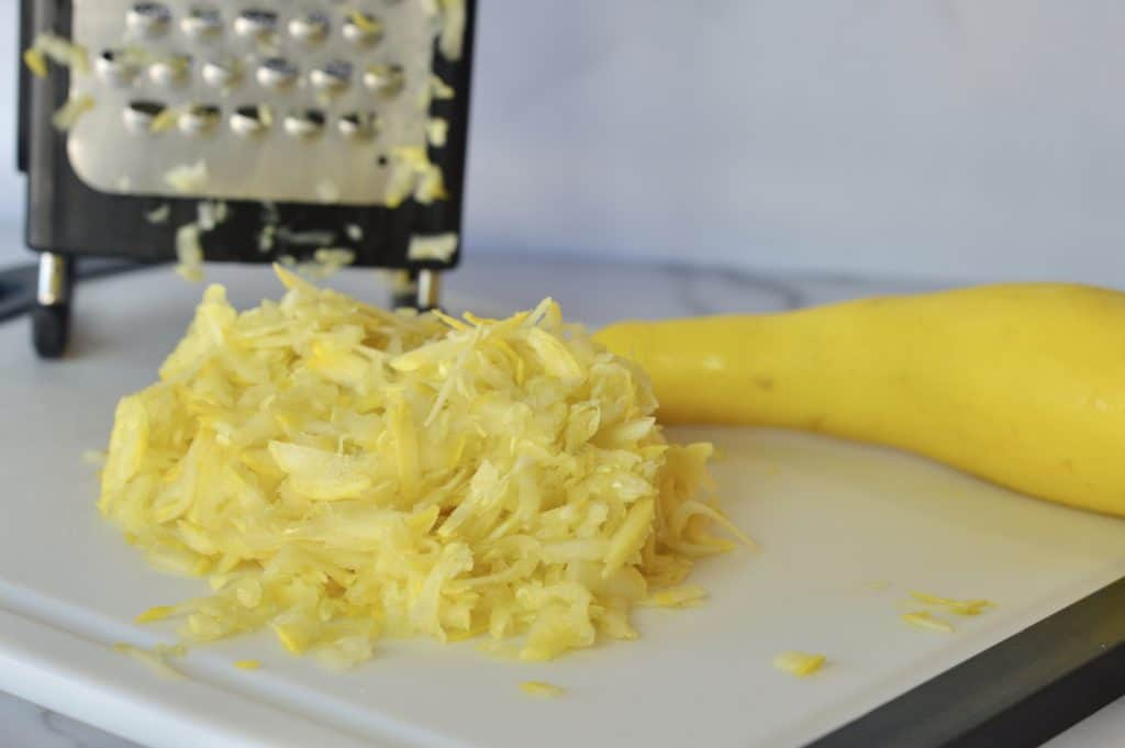 grated summer squash on a cutting board with box grater in the background