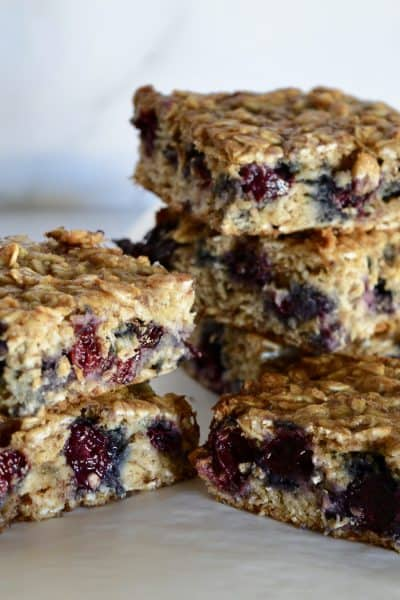 Blueberry Banana Oat Bars stacked on each other on a white background