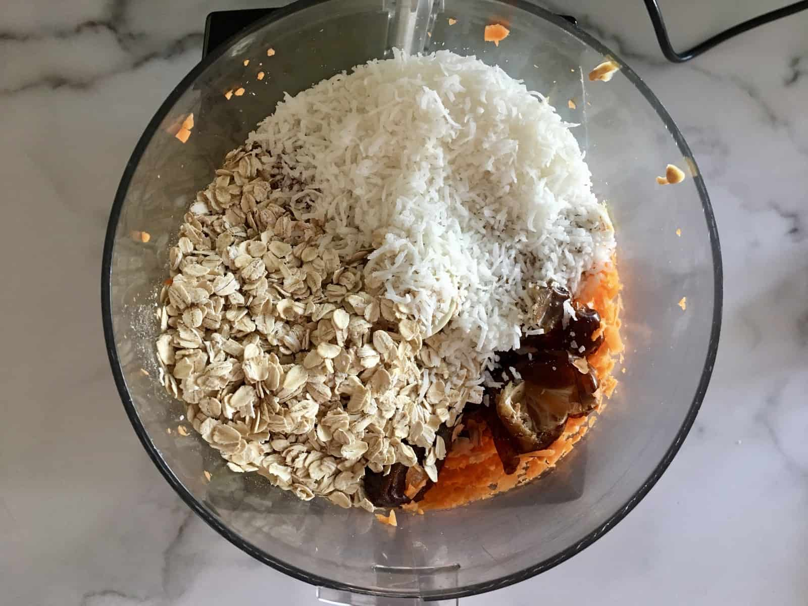overhead photo of food processor with oats, dates, shredded coconut, carrot, and peanut butter