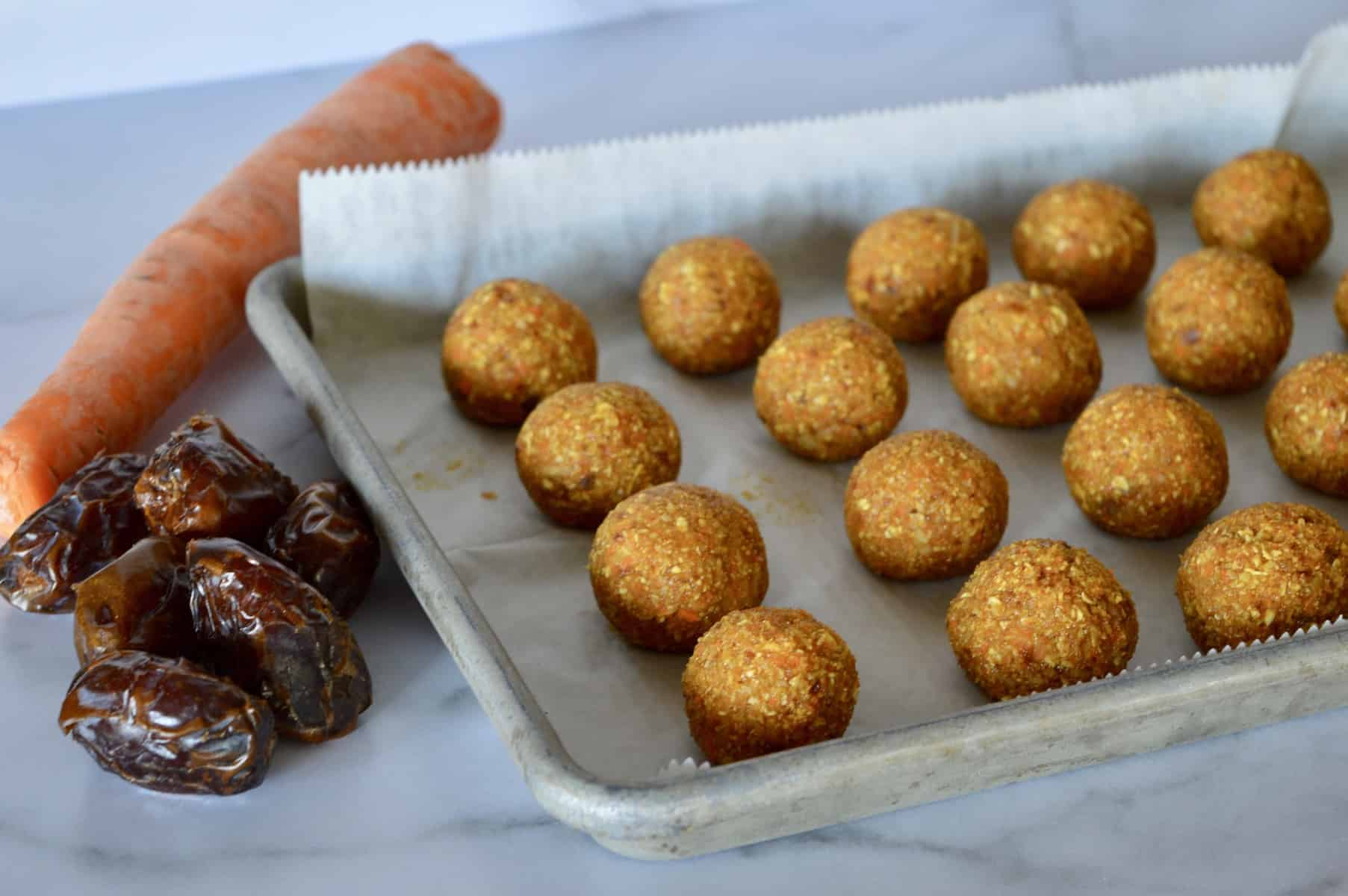energy balls on a parchment lined baking sheet with dates and carrot in background