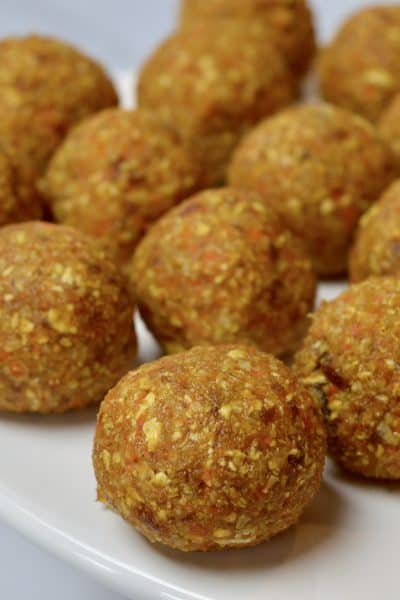 carrot coconut energy balls on a white pedestal with dates and a carrot in the background