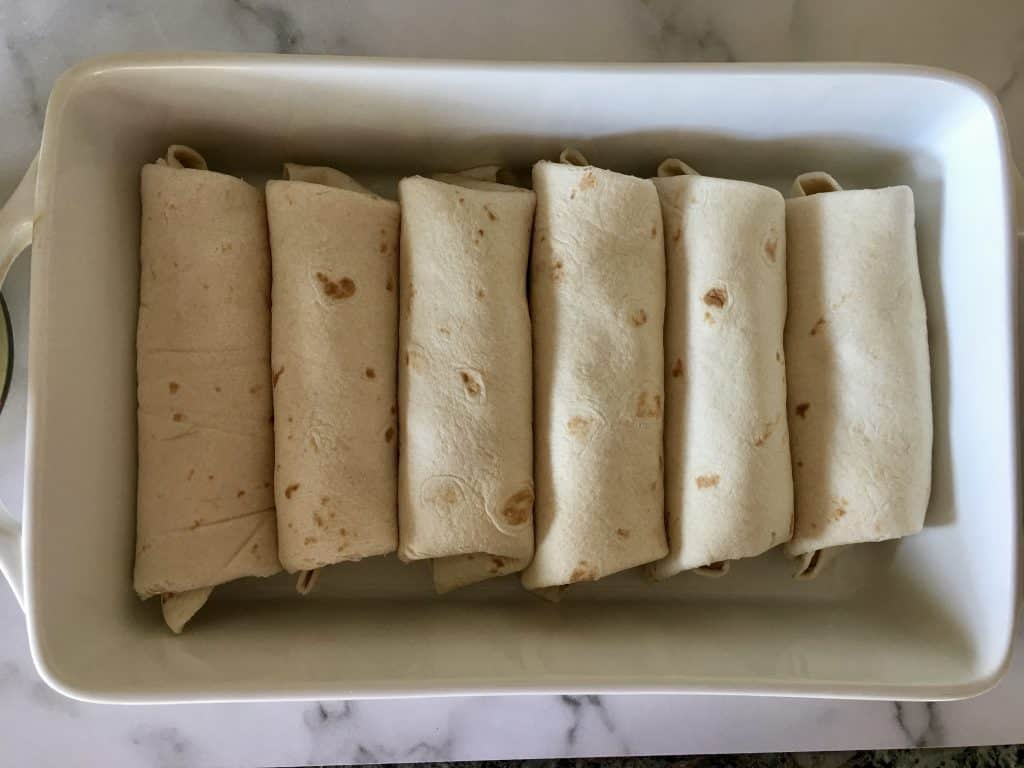 six burritos rolled in a white casserole dish.