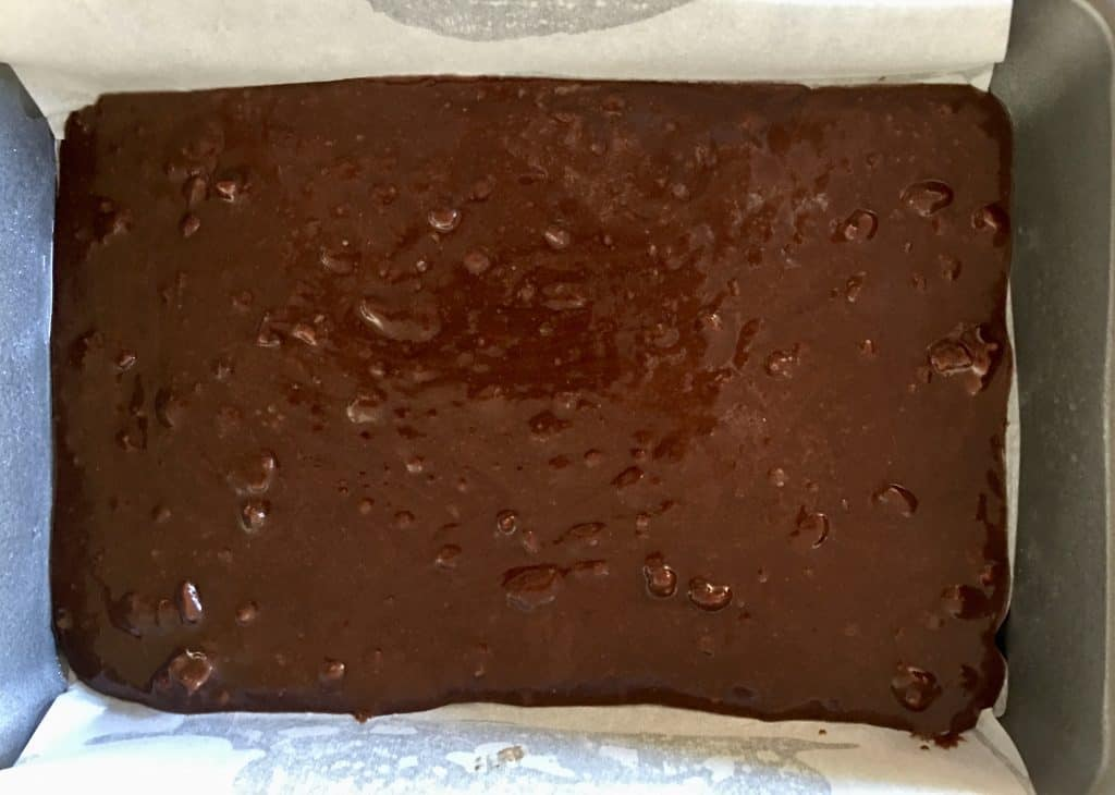 Brownie batter spread along the bottom of a baking pan lined with parchment paper.