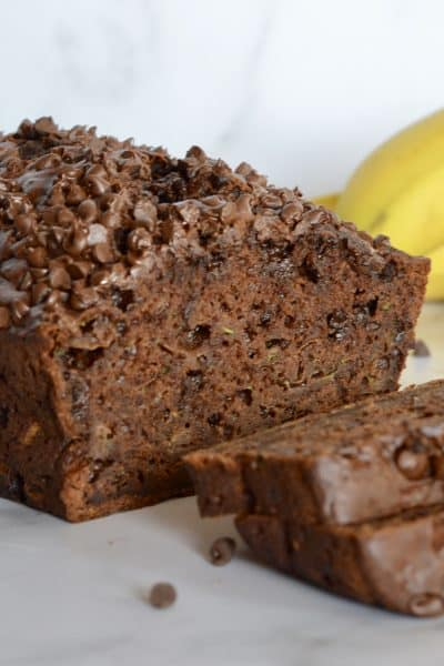 Chocolate Zucchini Banana Bread on a counter with bananas and a zucchini in the background