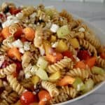 Whole Wheat Greek Pasta Salad with feta, tomatoes, cucumbers, and bell pepper in an white bowl.