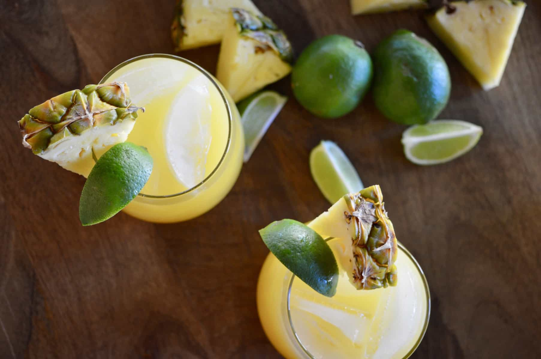 aerial view of pineapple margarita cocktails with lime wedges.
