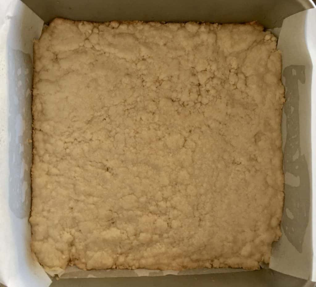 Shortbread pressed into the bottom of a greased and lined baking pan.