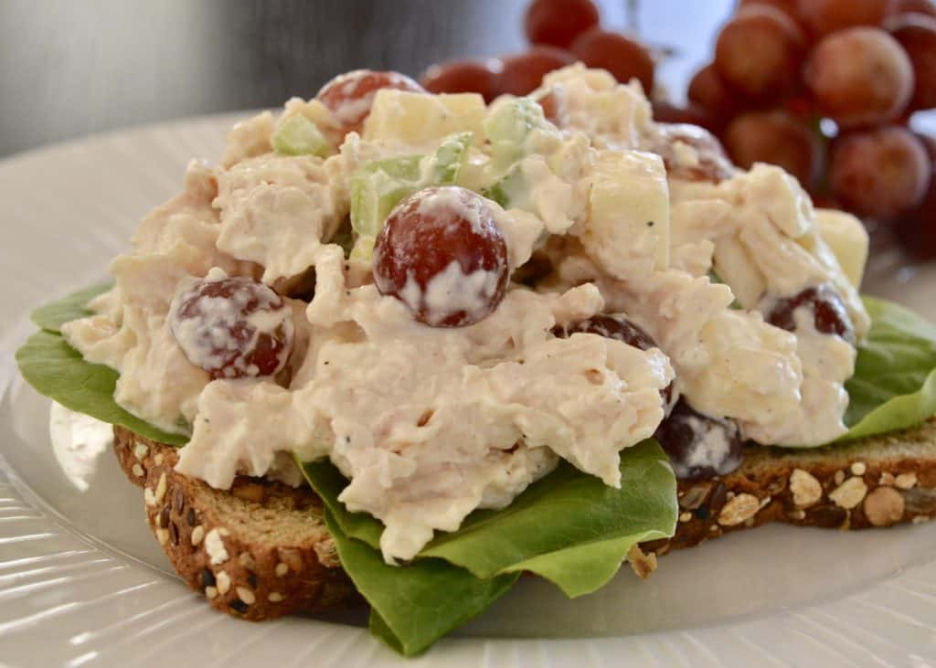 Rotisserie Chicken Salad on a piece of whole wheat toast with a side of red grapes.