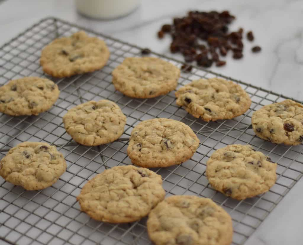 Cookies cooling on a rack with milk and raisins in the background.