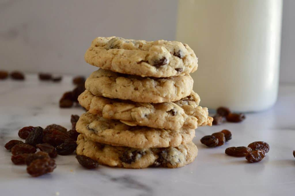 Oatmeal Raisin cookies stacked on a counter with a glass of milk.
