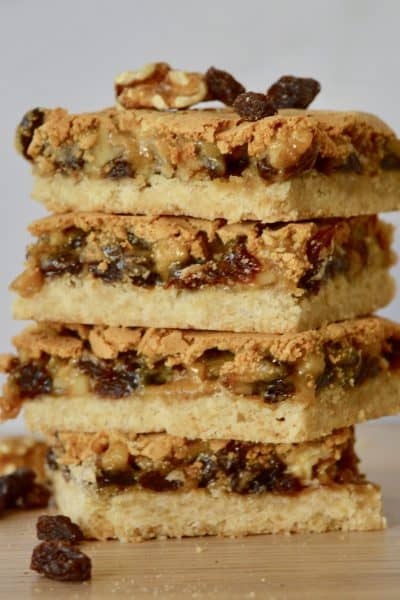 Butter Tart Squares with Walnuts and Raisins stacked on each other on a wooden table.