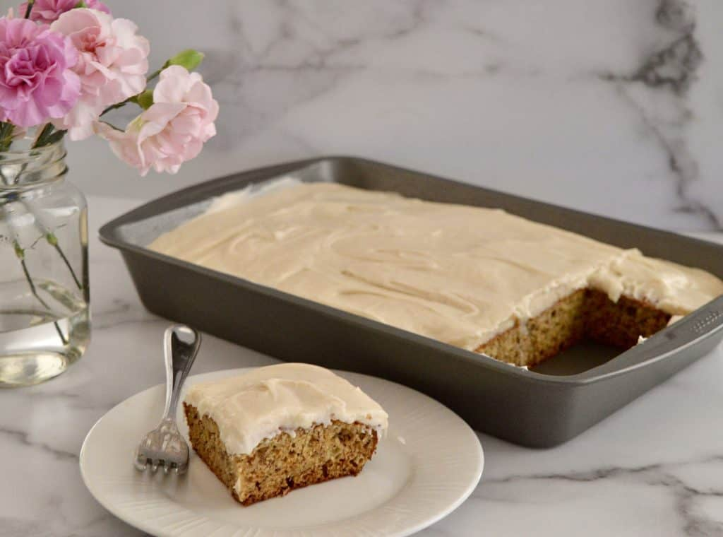 Brown butter banana cake on a white plate with carnations in the background.