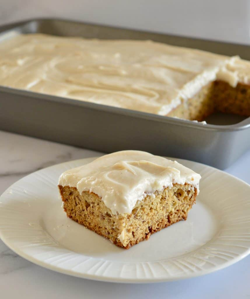 Brown butter banana cake on a plate with a tray of cake in the background.