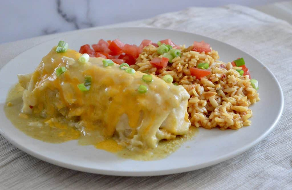 Green Chili Chicken Burritos on a white plate with mexican rice.