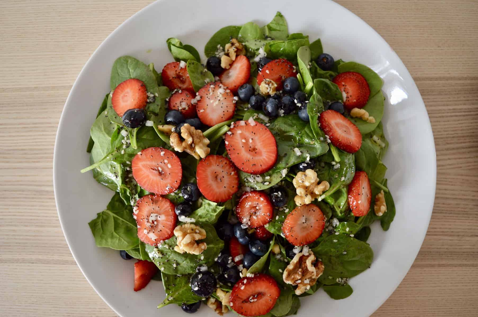 aerial view of strawberry blueberry spinach salad.