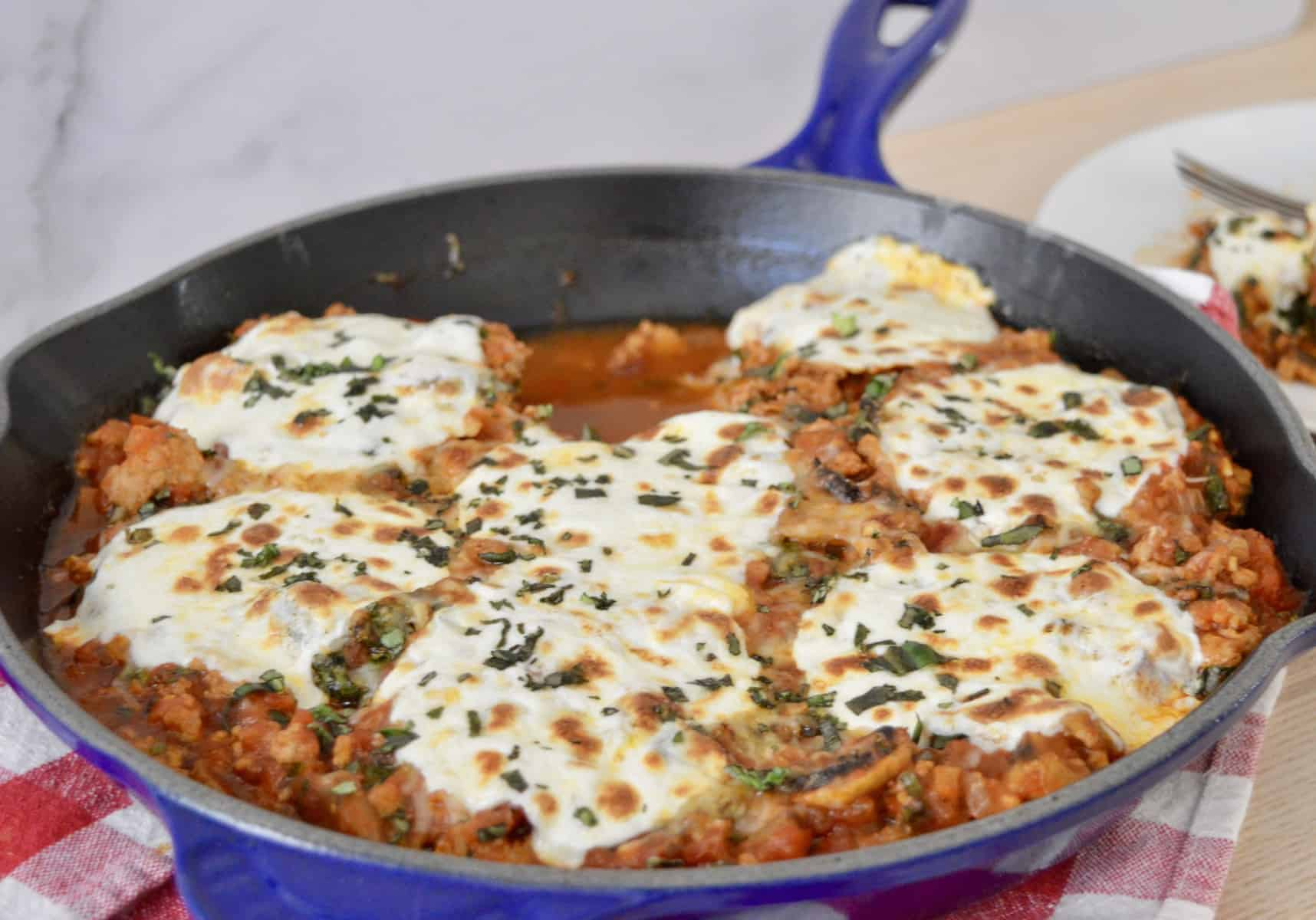 cast iron pan with sauce and cheese on top.