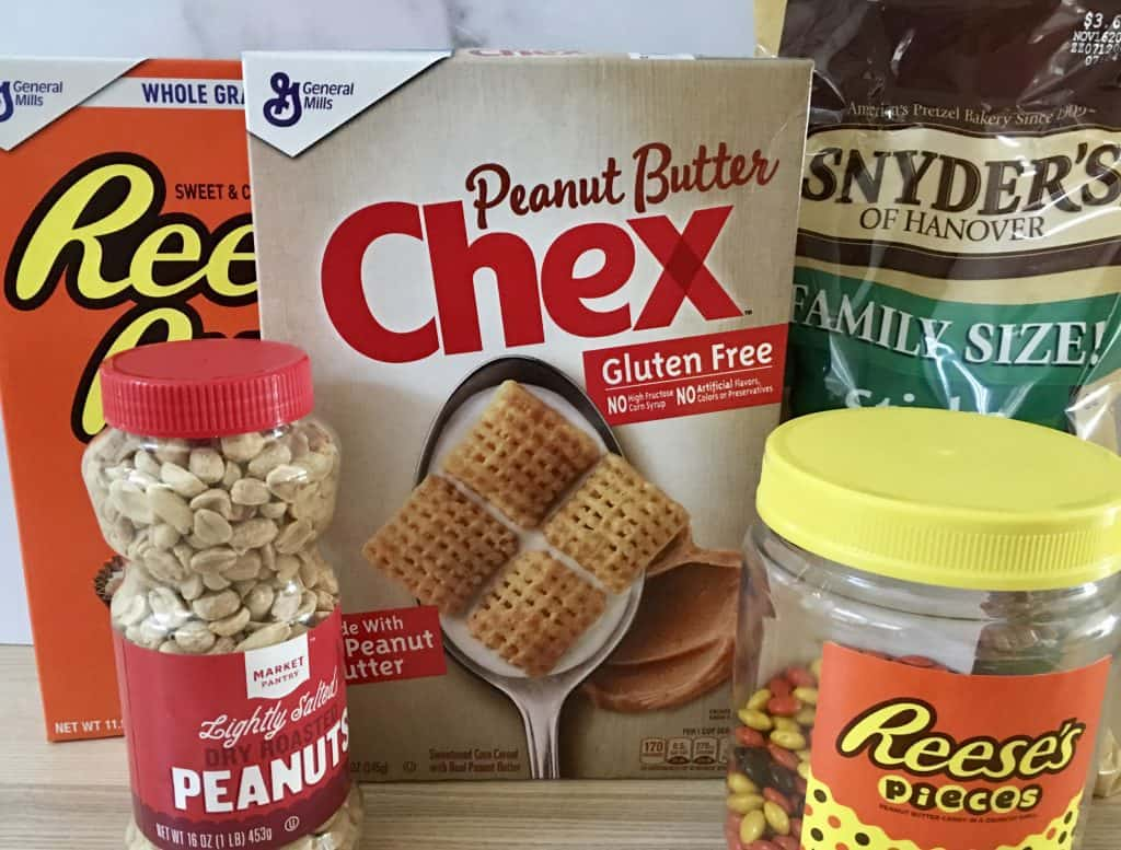 cereals, peanuts, Reese's pieces, and pretzels in their containers on a wood counter.