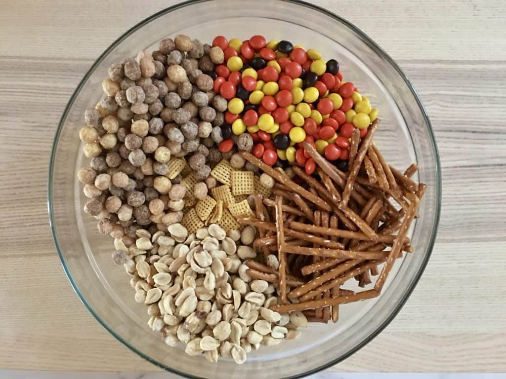 peanuts, Chex cereal, pretzels, and Reese's pieces in a large glass bowl.