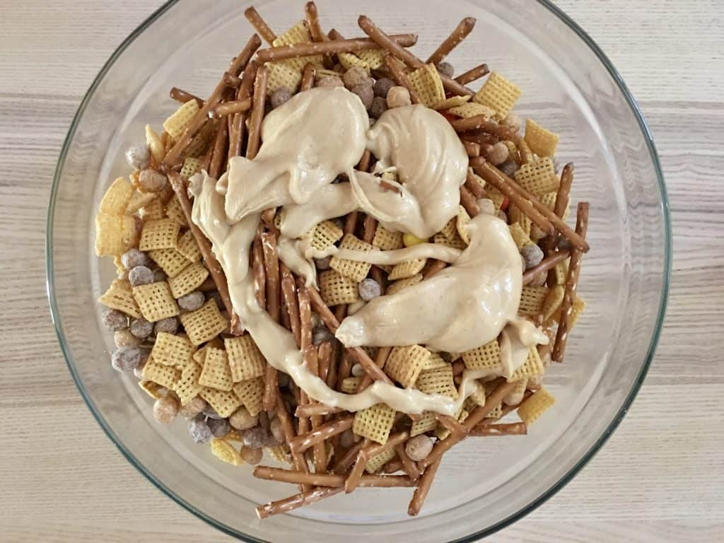 peanut butter white chocolate sauce drizzled over top of the peanut butter muddy buddies.