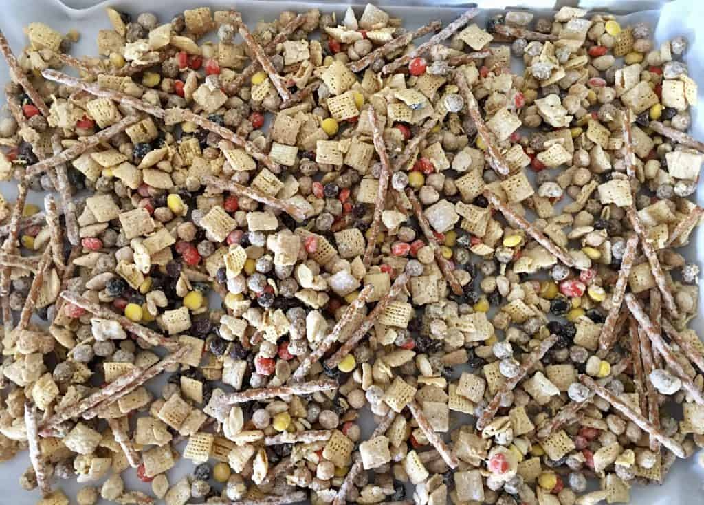 Muddy Buddie peanut butter snack mix drying on a parchment sheet.