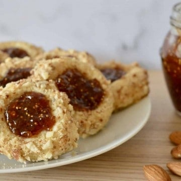 Italian Fig and almond cookies on a plate with fig jam in the background.