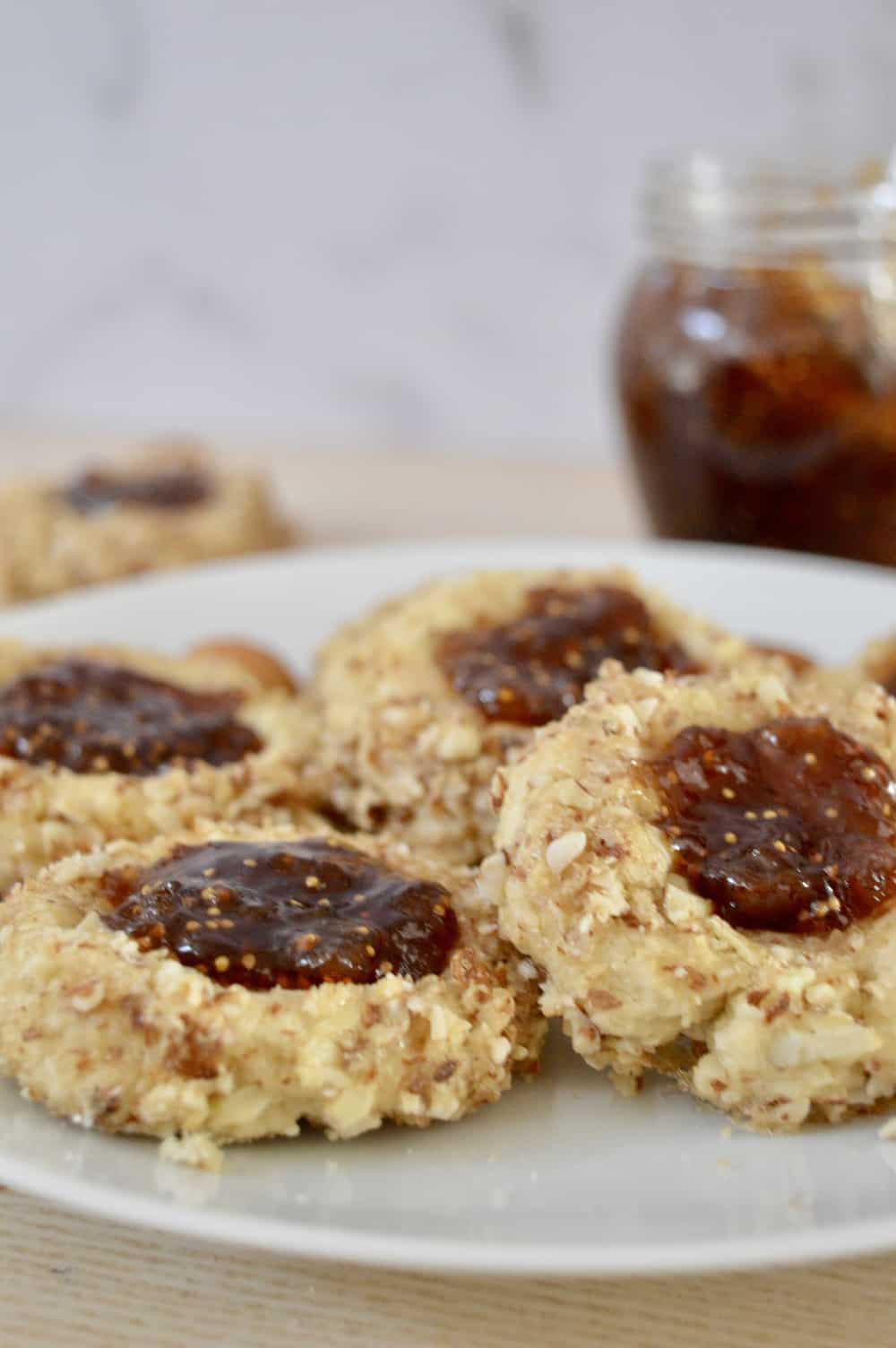 Italian Fig and Almond Thumbprint Cookies on a white plate with fig spread in the background.