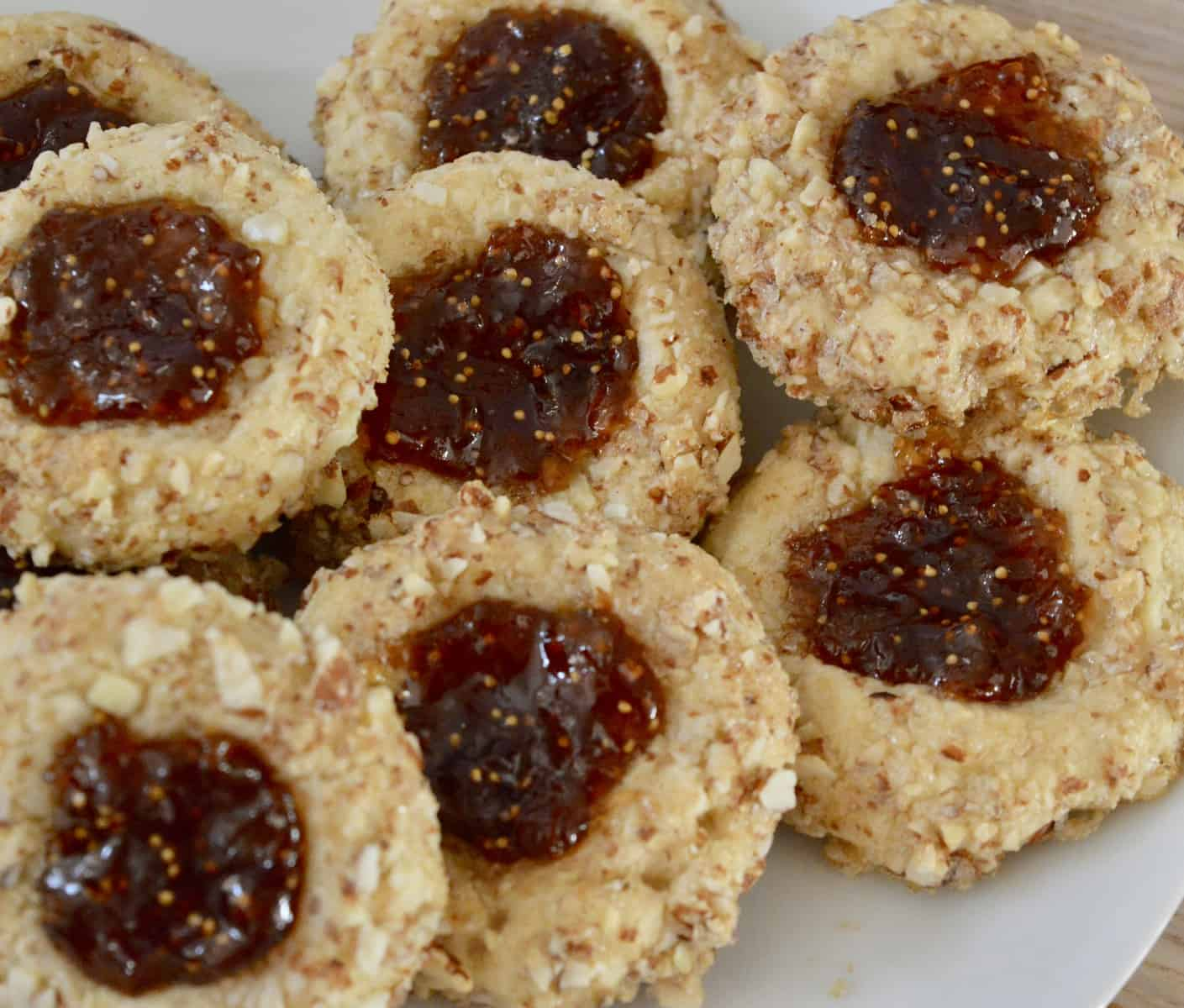 overhead view of Italian thumbprint cookies with fig spread and almonds.