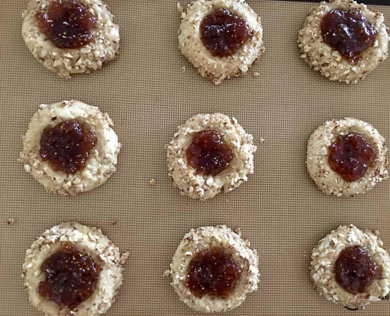 jam filled cookies on baking sheet.