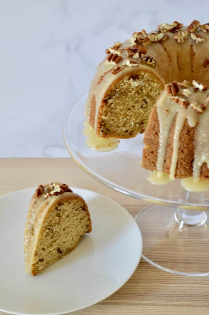 Bourbon Pecan Banana Bundt Cake with a Bourbon Butter Glaze! So moist and delicious, it's the best way to use up those ripe bananas! #bourbonpecan #bananabundtcake with bourbon butter frosting on a glass pedestal.