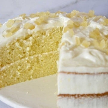 Limoncello Ricotta Cake on a white pedestal with a piece cut out of it.