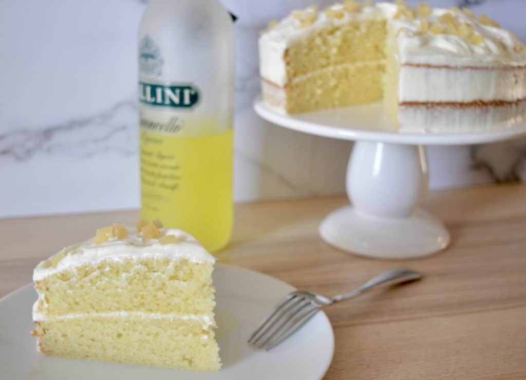 Limoncello Ricotta Cake on a pedestal with a bottle of Limoncello liqueur in the background.