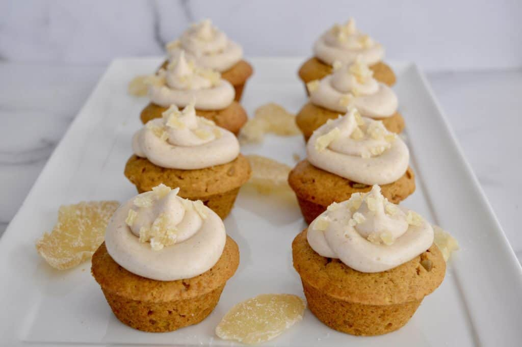 pumpkin ginger cupcakes lined up on a white serving platter.