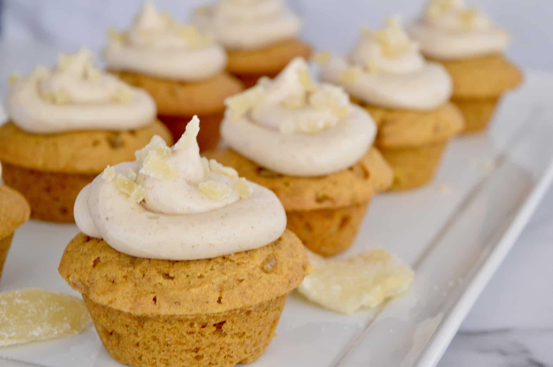 pumpkin ginger cupcakes on a white serving platter.