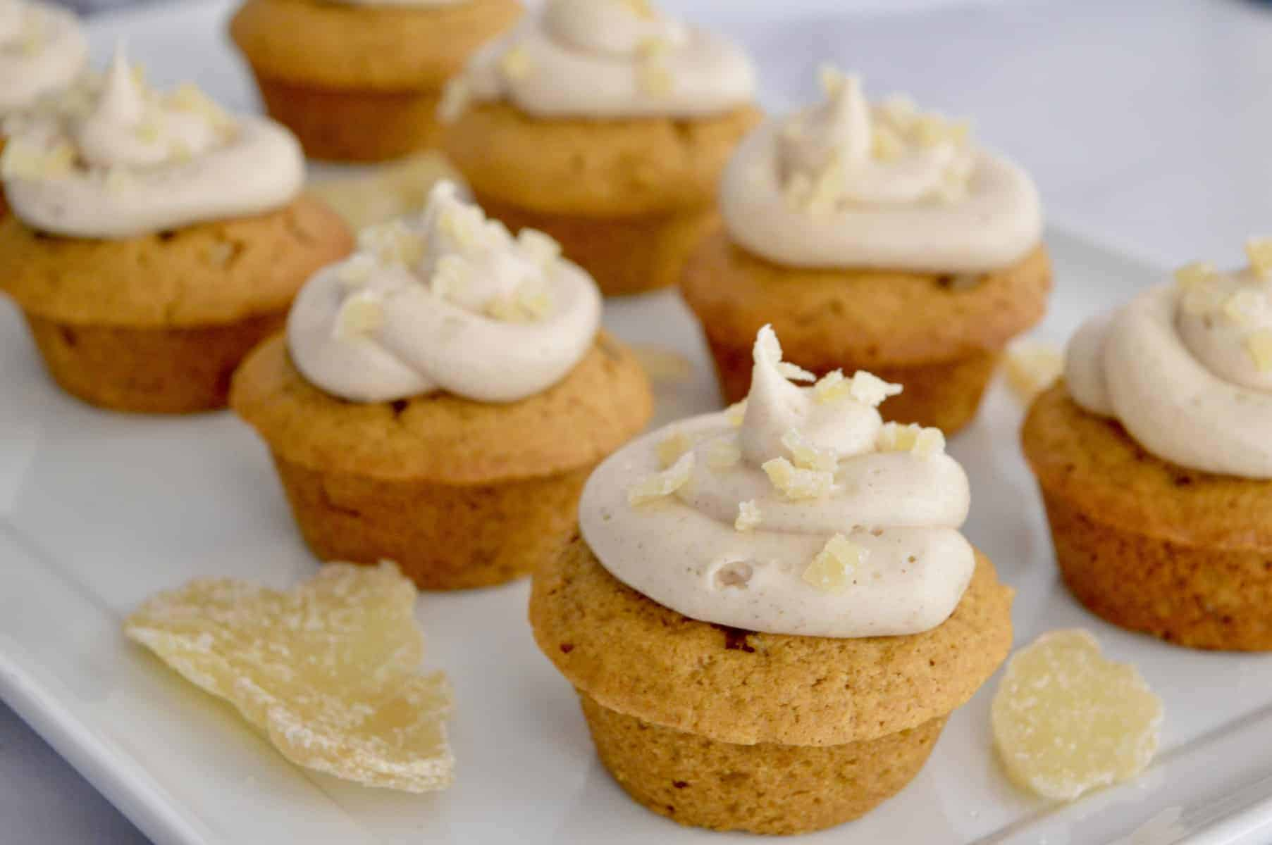 pumpkin ginger cupcakes with cream cheese frosting on a white platter with candied ginger.
