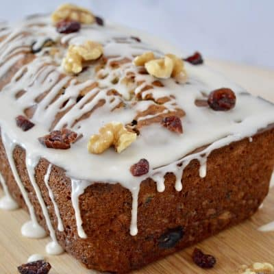 Cranberry Walnut Banana Bread on a wooden cutting board.