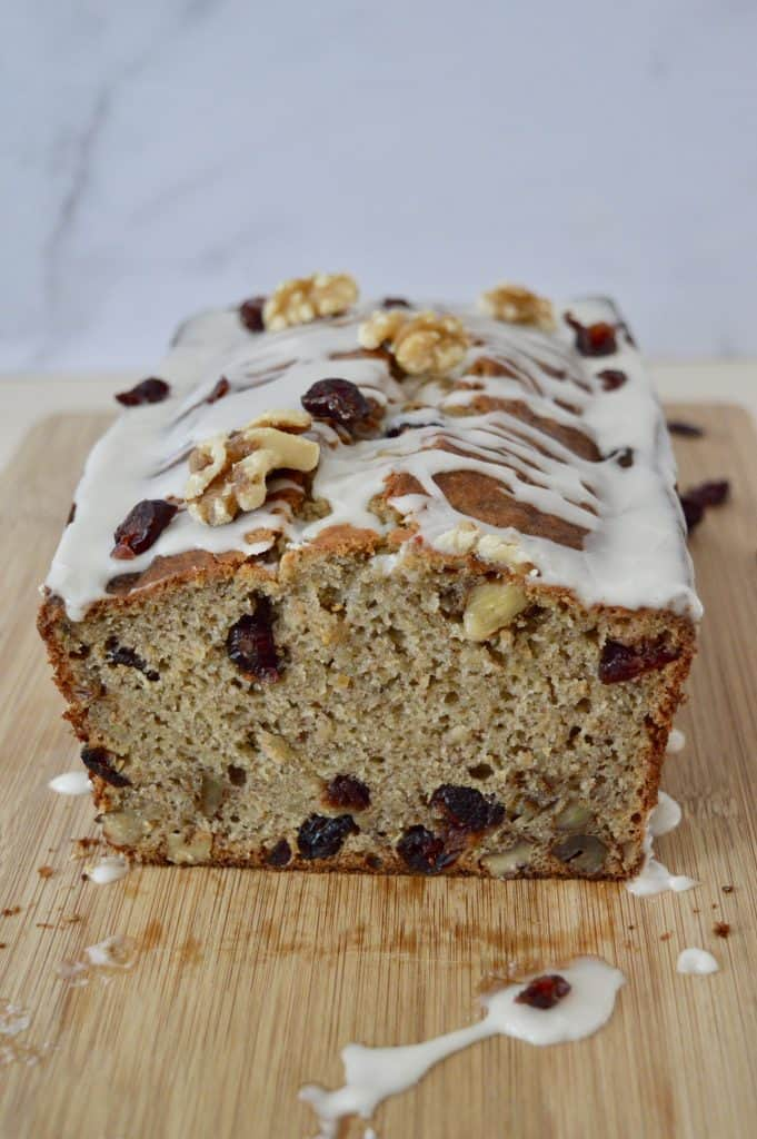 Cranberry Walnut Banana Bread with glaze on a wooden cutting board.