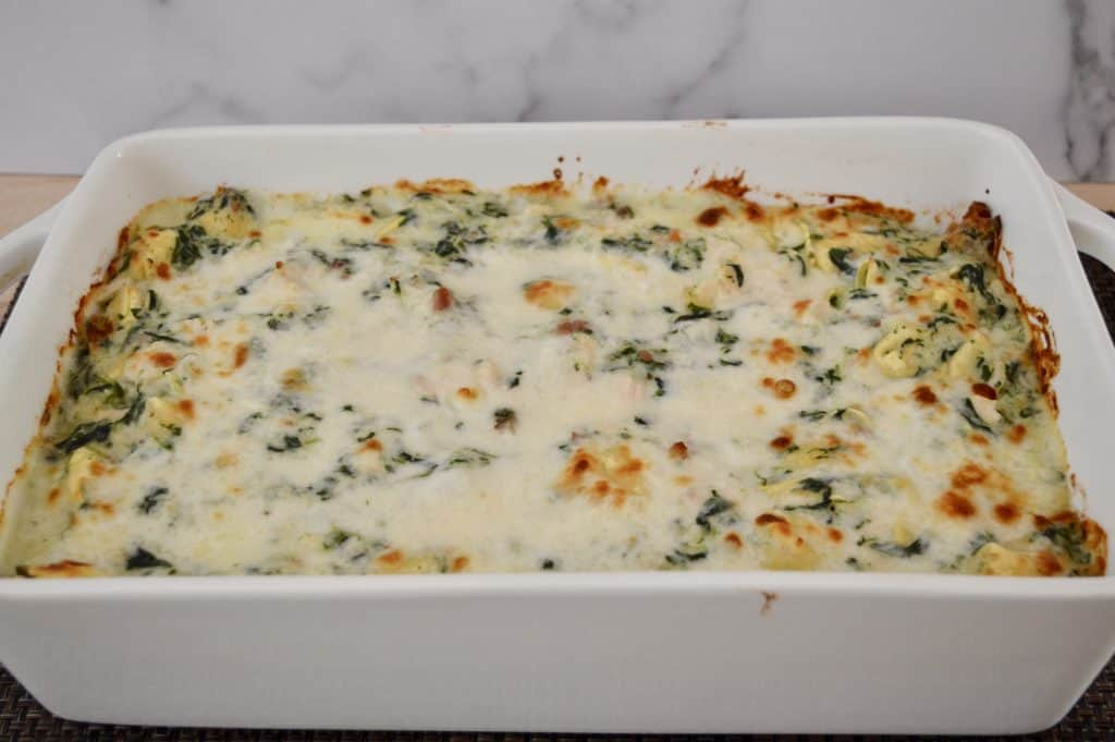 white baking pan with chicken bacon spinach tortellini inside.