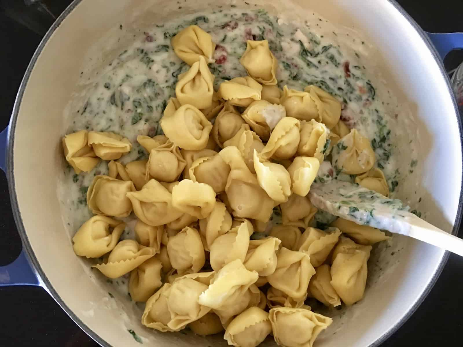 tortellini on top of spinach alfredo mixture.