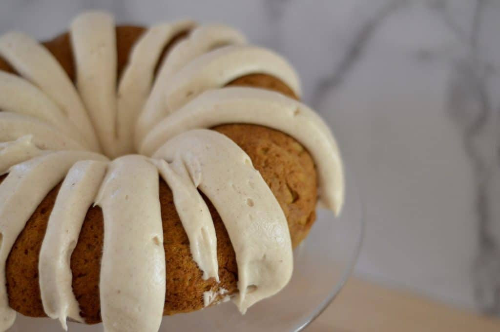 pumpkin spice bundt cake with cream cheese frosting on a glass pedestal.