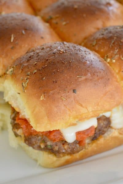 mini baked meatball sandwiches on a white serving platter.