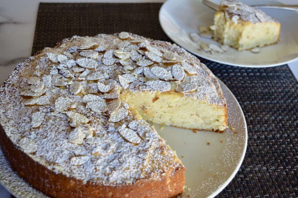Almond Ricotta Cake on a plate with a slice in the background.